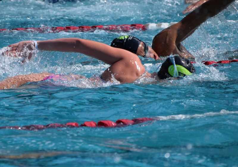 молодежь плавает в бассейне