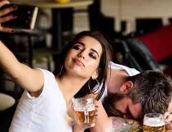 девушка фотографируется с пьяным парнем